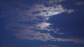 La luna misteriosa che si nasconde dietro le nuvole, brillanti brillantemente in cielo notturno scuro, sogna stock footage