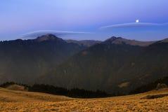 La luna rised e lucidando sopra l'alta montagna. Fotografie Stock Libere da Diritti