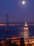 La luna sobre el edificio del transbordador y el puente de la bahía Foto de archivo libre de regalías