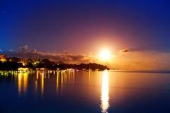 La luna sopra il mare e riflessione in acqua. Immagini Stock