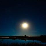 La luna y las estrellas en cielo nocturno reflejaron en el río Imágenes de archivo libres de regalías