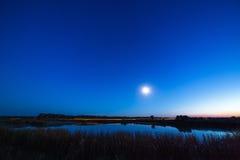 La luna y las estrellas en el cielo nocturno reflejaron en el río Fotografía de archivo libre de regalías
