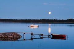 La lune brille au-dessus d'un beau paysage suédois de lac la nuit Images stock
