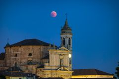 La lune rouge apocalyptique et l'église Photographie stock