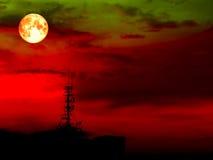 la lune superbe et la tache floue de plein sang ombragent le pilier de signal sur le toit Images libres de droits