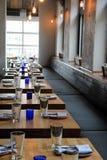 La lunghezza di parecchie tavole di legno ha messo per la cena, con i supporti di candela blu luminosi nel centro di ciascuno Fotografia Stock