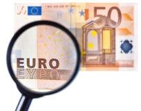 La lupa enfoca billete de banco Imagen de archivo libre de regalías