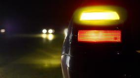La luz anaranjada el intermitente que destellaba en el coche deportivo parqueó en lado en la noche metrajes