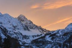 La luz anaranjada ilumina el cielo sobre la montaña imagen de archivo libre de regalías