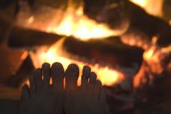 La luz de Defracted abraza los dedos del pie delante de la hoguera fotos de archivo