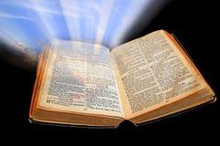 La luz de la biblia brilla fuera de oscuridad Fotos de archivo