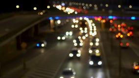 La luz de las linternas del coche, el movimiento de coches en la ciudad en la noche, el movimiento de coches en la carretera blur almacen de metraje de vídeo
