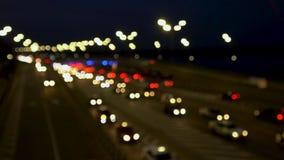 La luz de las linternas del coche, el movimiento de coches en la ciudad en la noche, el movimiento de coches en la carretera blur metrajes