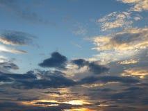 la luz de oro del sol de la tarde brilla a través de las nubes en el cielo Fotos de archivo