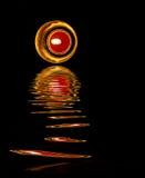 La luz de una vela y la reflexión de la luz de una vela agitan la línea en el agua su Foto de archivo