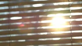 La luz del sol borrosa abstracta pasa a través de las persianas de ventana metrajes
