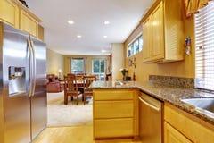 La luz entona el interior de la cocina con el refrigerador de acero moderno de las puertas dobles Fotos de archivo libres de regalías