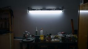 La luz está encendido sobre el banco de trabajo almacen de metraje de vídeo