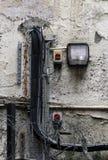 La luz externa de la seguridad montó en una pared externa lamentable vieja con el cableado y el alambre de púas sucios imagen de archivo libre de regalías