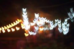 La luz, mariposa hermosa del bokeh formó y falta de definición en la noche Foto de archivo