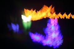 La luz, mariposa hermosa del bokeh formó y falta de definición en la noche Imágenes de archivo libres de regalías