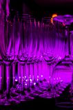 La luz púrpura reflejó en las filas de vidrios limpios vacíos en el contador de la barra Interior del pub o de la barra en la noc imagenes de archivo