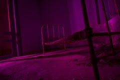 La luz pintada en rosa abandonó la cama en sitio oscuro Pieza de Halloween Foto de archivo