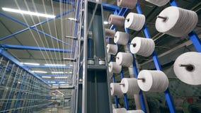 La máquina automatizada encanilla el hilo sobre los ovillos grandes en una fábrica almacen de video