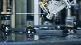 La máquina automatizada pone los casquillos en las botellas con el alcohol, cierre para arriba almacen de video