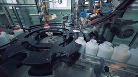 La máquina automatizada pone los casquillos en mientras que las botellas, converyor de la fábrica almacen de metraje de vídeo