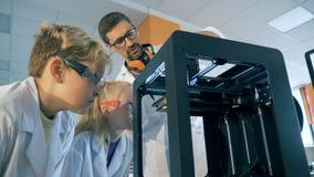 La máquina científica está siendo mostrada a los niños por un especialista del laboratorio almacen de video