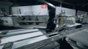 La máquina de atascamiento está atando las cubiertas de papel a los bordes metrajes