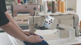 La máquina de coser automática en una fábrica de la materia textil con el hilo amarillo arrolla almacen de metraje de vídeo