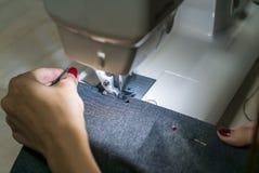 La máquina de coser cose la máquina de coser de las manos de las mujeres Imagen de archivo libre de regalías