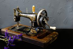 La máquina de coser del vintage se está colocando en la tabla blanca fotografía de archivo libre de regalías
