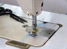 La máquina de coser y hacia fuera enfoca los accesorios de costura, tijeras Clippers Fotografía de archivo libre de regalías