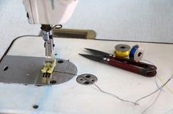 La máquina de coser y los accesorios, las tijeras Clippers con el azul y el amarillo de costura roscan en las bobinas Foto de archivo