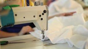 La máquina de coser y la tela blanca, mano de la mujer detrás de la costura, dan la hembra, fabricación de costura, fábrica de la almacen de metraje de vídeo