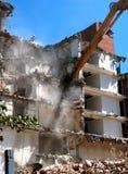 La máquina de la demolición del edificio tira hacia abajo una pared Fotografía de archivo libre de regalías