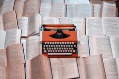 La máquina de escribir de la visión superior está en muchos libros abiertos Foto de archivo libre de regalías