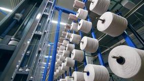 La máquina de la fábrica arrolla la fibra sobre las bobinas rodantes en una instalación almacen de video
