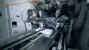 La máquina de la fábrica empuja los libros impresos en un transportador metrajes