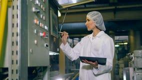 La máquina de la fábrica está consiguiendo controlada por un experto femenino almacen de metraje de vídeo