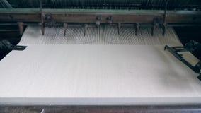 La máquina de la fábrica está cosiendo la tela blanca almacen de metraje de vídeo