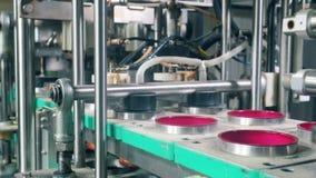La máquina de la fábrica está cubriendo los envases con la hoja Equipo de la f?brica de la comida almacen de metraje de vídeo