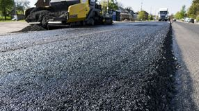 La máquina de funcionamiento de la pavimentadora del asfalto del trabajador durante la construcción de carreteras y la reparación imagen de archivo libre de regalías
