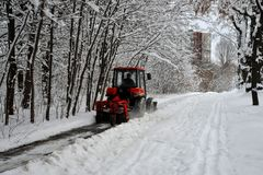 La máquina de la nieve, tractor rojo limpia la nieve de la nieve en el fondo del bosque imagenes de archivo