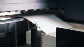 La máquina de la prensa toma la hoja de papel en la acción en la cadena de producción de la impresión almacen de metraje de vídeo