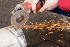 La máquina de pulir angular corta el metal con las chispas Imágenes de archivo libres de regalías