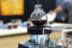 La máquina del café en tienda con el cliente empañó el fondo Imágenes de archivo libres de regalías